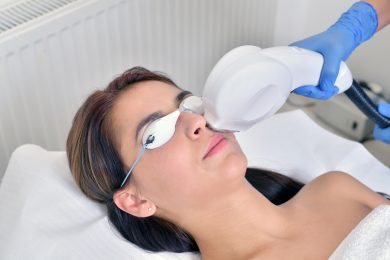 Beautiful young woman lying on a table with protect glasses on eyes getting a laser skin treatment